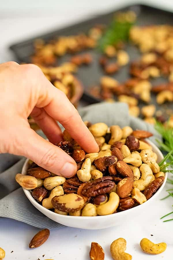 Hand reaching from the left into a white bowl filled with rosemary savory spiced nuts