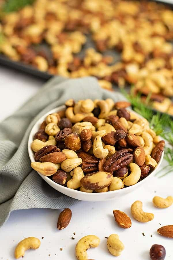 Close up on a white bowl filled with rosemary savory spiced nuts with a grey napkin and baking sheet full of nuts in the background