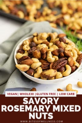 Close up on a white bowl filled with rosemary savory spiced nuts with a grey napkin and baking sheet full of nuts in the background with pinterest text on the bottom of the photo