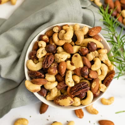 Overhead shot of white bowl filled with rosemary savory spiced nuts over a grey napkin with a rosemary sprig to the right of the bowl