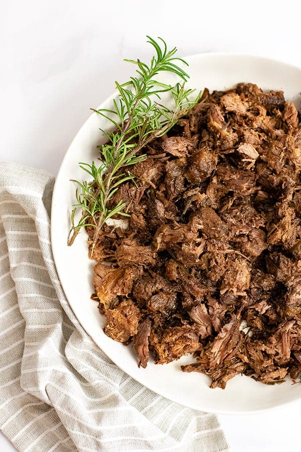 arge bowl filled with slow cooker balsamic beef over a brown striped napkin