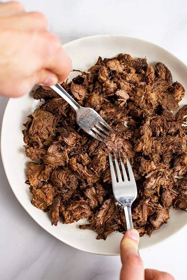 Two forks shredding the slow cooker balsamic beef
