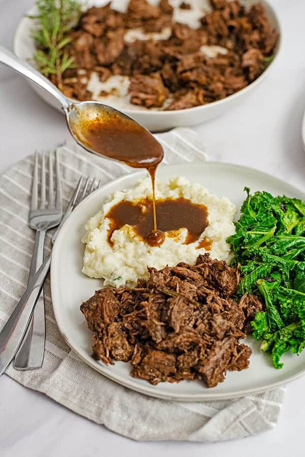 Dinner plate filled with slow cooker balsamic beef, mashed cauliflower, gravy and kale