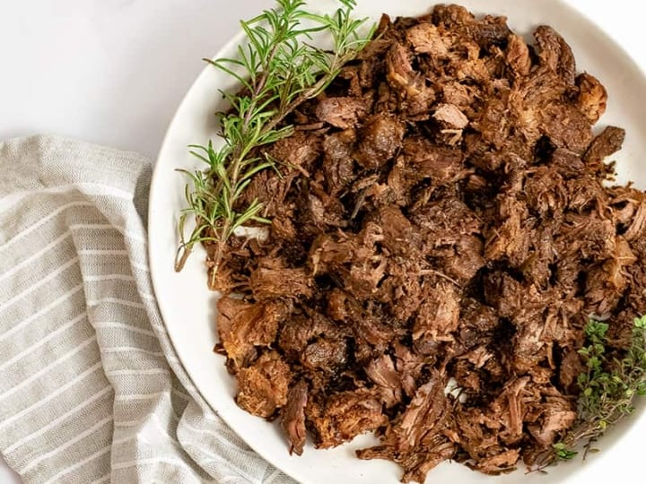 Overhead shot of large plate of slow cooker balsamic beef with fresh rosemary sprigs on the plate over a brown striped napkin