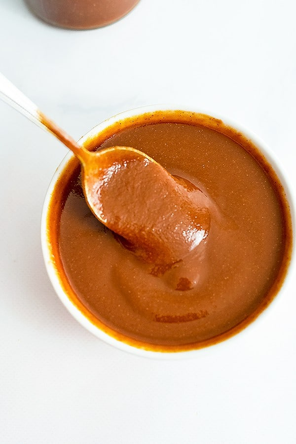 White bowl of Whole30 BBQ Sauce with a spoon full of bbq lifting from the bowl.