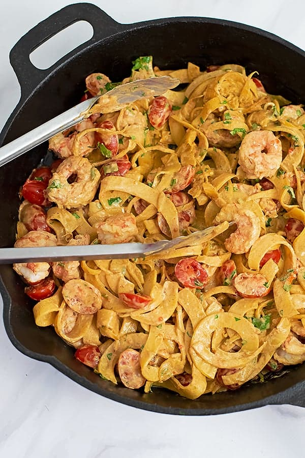 Cast iron skillet filled with Whole30 Creamy Cajun Shrimp Pasta recipe with a pair of silver tongs in the skillet