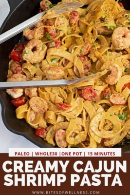 Cast iron skillet filled with Whole30 Creamy Cajun Shrimp Pasta recipe with a pair of silver tongs in the skillet with pinterest text on the bottom of photo