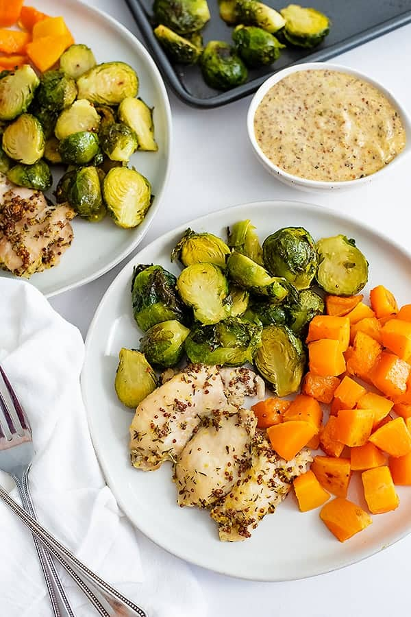 Sheet pan dijon mustard chicken thighs and vegetables plated on a white plate with a white napkin on the left of the plate and a dipping sauce in the background