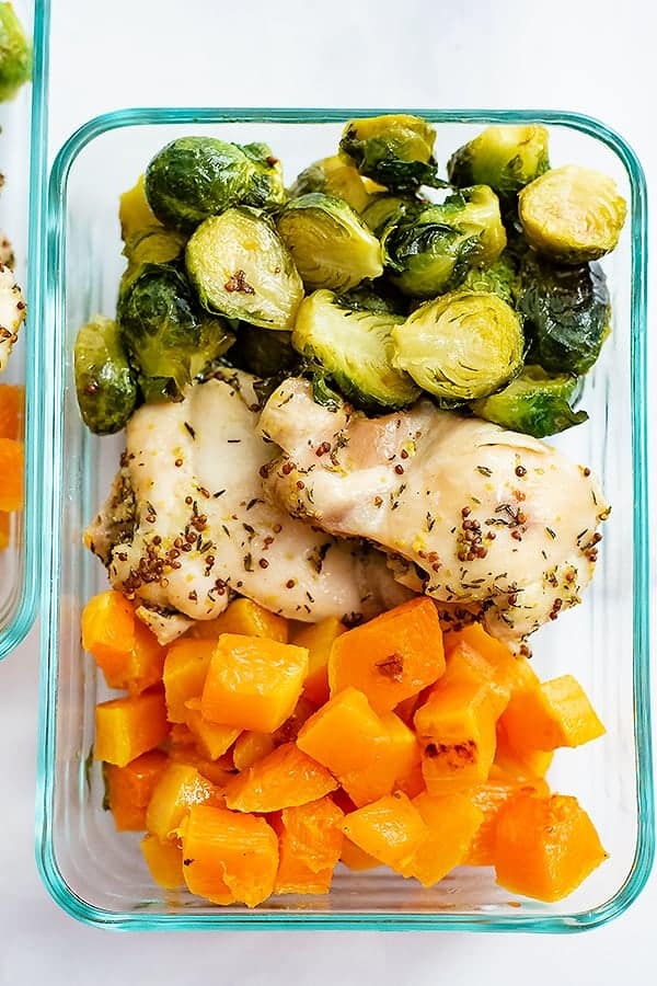 Pyrex container filled with meal prepped sheet pan dijon mustard chicken and vegetables ( brussel sprouts and butternut squash)