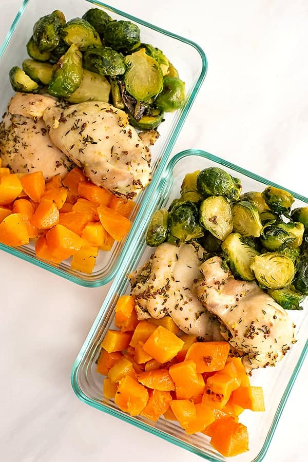 Two pyrex container filled with meal prepped sheet pan dijon mustard chicken and vegetables ( brussel sprouts and butternut squash)