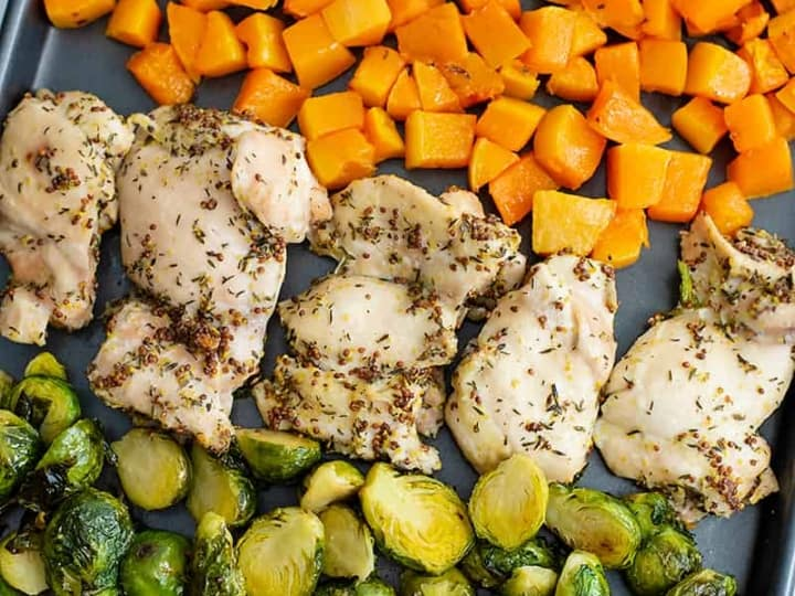 Sheet pan filled with butternuts squash cubes, dijon mustard chicken thighs and halved brussel sprouts