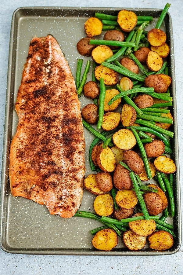 Sheet pan filled with cajun salmon sheet pan meal with an entire salmon fillet, potatoes and green beans