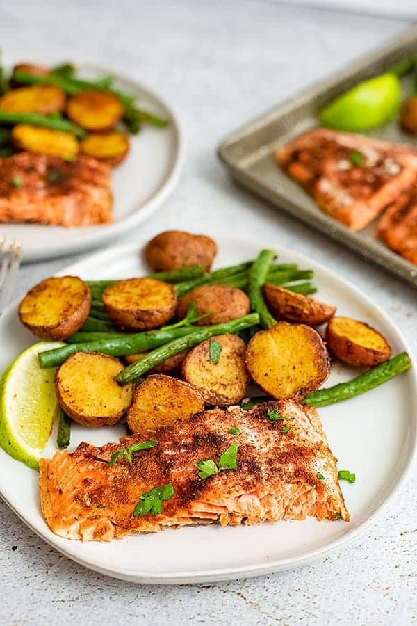 Close up of a plate of cajun salmon sheet pan dinner with the sheet pan in the background