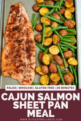 Sheet pan filled with cajun salmon sheet pan meal with an entire salmon fillet, potatoes and green beans. Pinterest text on the bottom of the photo