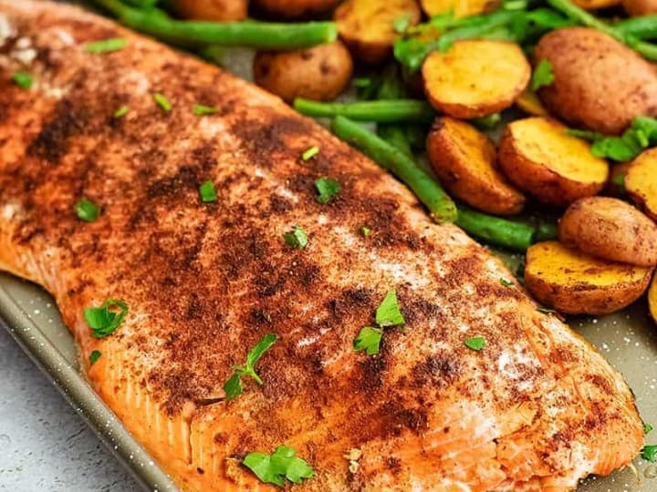 Close up of Sheet pan filled with cajun salmon sheet pan meal with an entire salmon fillet, potatoes and green beans