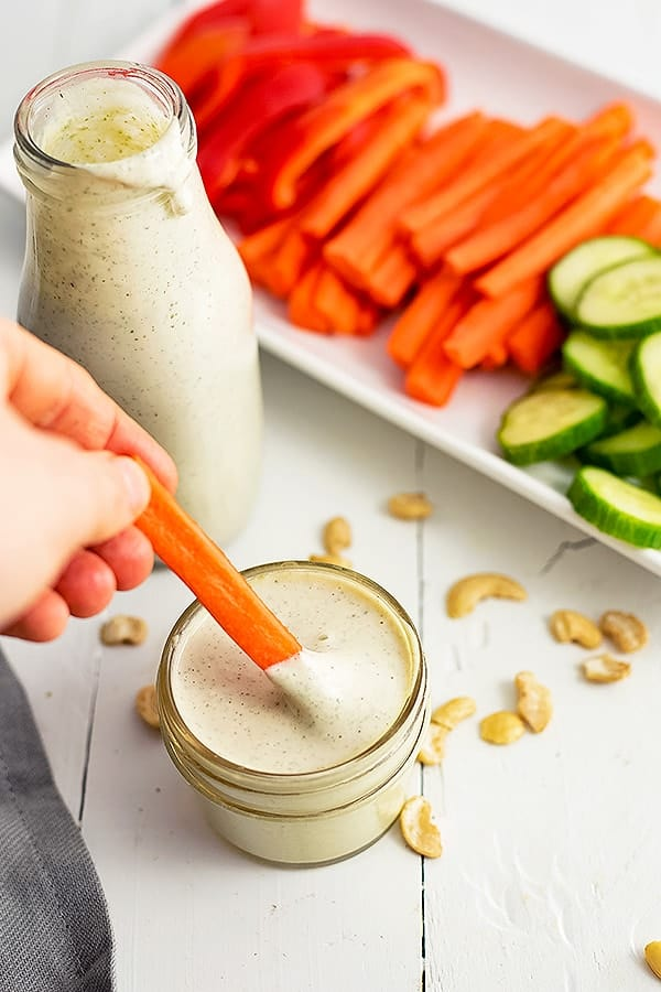 Small jar of dairy free ranch dressing with a carrot being dipped into the dressing. A bottle of dressing and a plate of veggies in the background