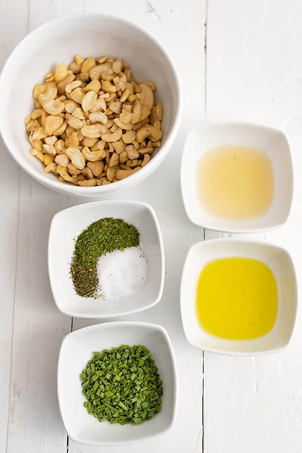 Ingredients for dairy free ranch dressing (cashews, apple cider vinegar, garlic olive oil, dried parsley, dried dill, salt and dried chives) all in small ramekins or bowls