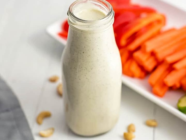 Bottle of dairy free ranch dressing on a white table with cashews on the table around the bottle. Platter of veggies in the background