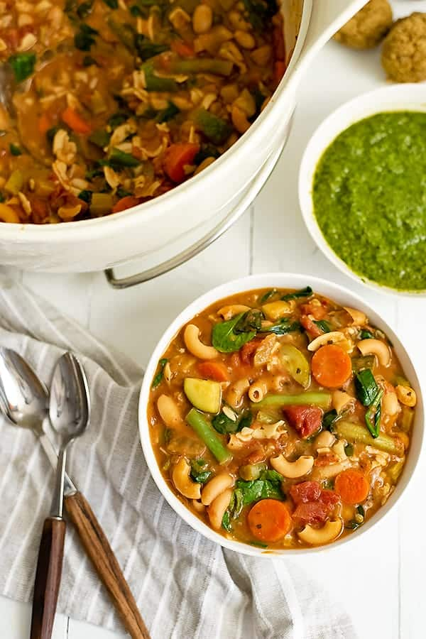 Overhead shot of a bowl of vegan minestrone soup with the pot of soup and pesto in the background. Two wooden handled spoons resting on a grey striped napkin to the left of the bowl.