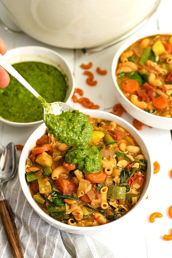 Spoonful of pesto being added to a bowl of vegan minestrone soup with the bowl of pesto in the background