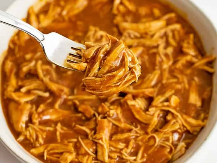 Large bowl filled with instant pot bbq chicken with a fork holding the shredded chicken over the bowl.