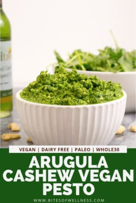 Close up on a bowl of arugula cashew vegan pesto with pinterest text on the bottom