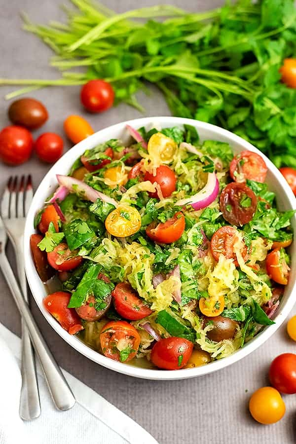 Overhead shot of a large white bowl filled with Greek Spaghetti Squash Salad. Tomatoes and parsley surround the bowl and there is a white napkin and two forks off to the left.