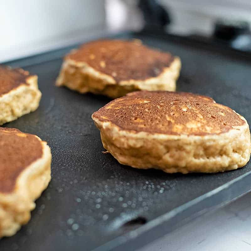 Gluten free protein pancakes cooking on a skillet