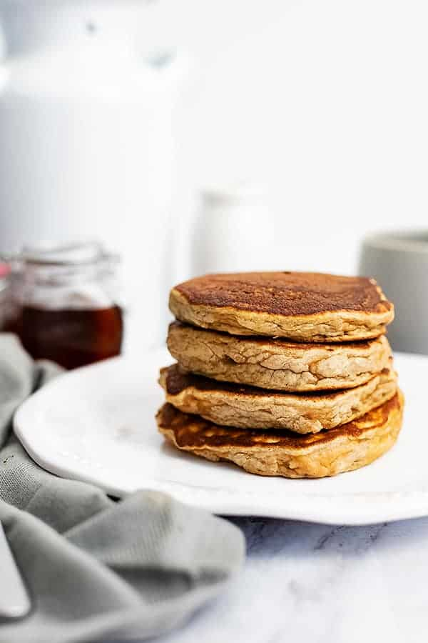 Large stack of gluten free protein pancakes on a white plate with a bottle of syrup in the background