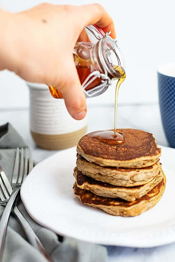 Hand pouring syrup over gluten free protein pancakes
