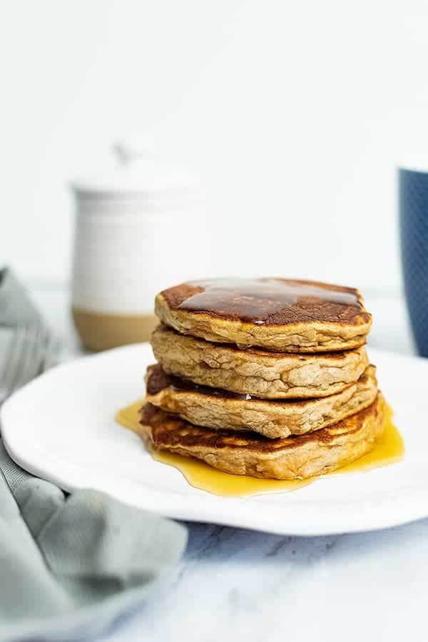 Stack of gluten free protein pancakes with syrup dripping down. White ceramic jar in the background