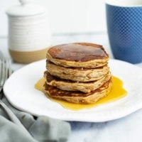 Stack of gluten free protein pancakes with syrup dripping down. Blue coffee cup in the background