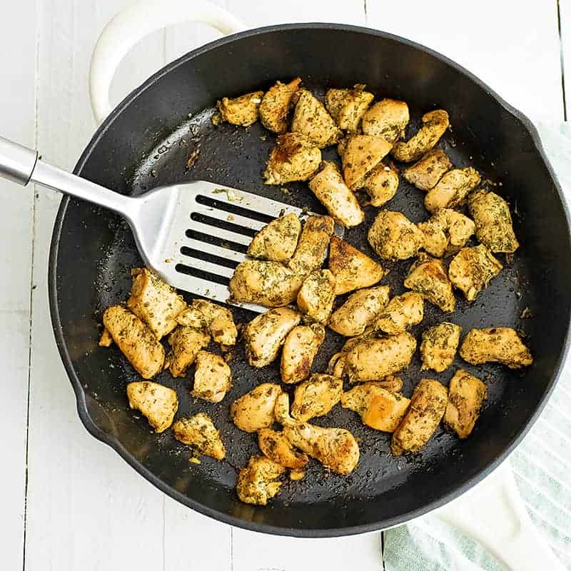 Overhead shot of a cast iron skillet filled with ranch chicken bites with a silver spatula in the pan with the chicken