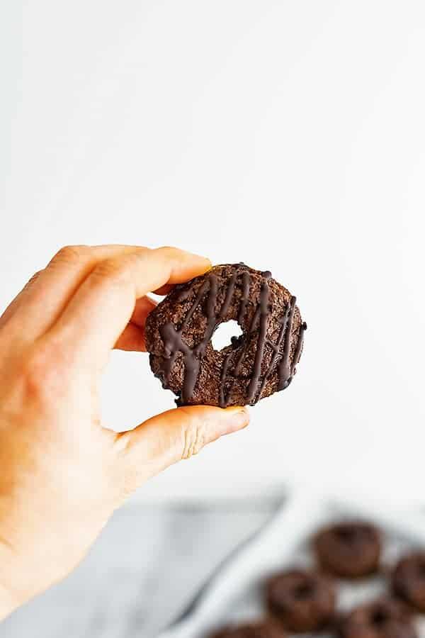 Hand holding a single sweet potato donut