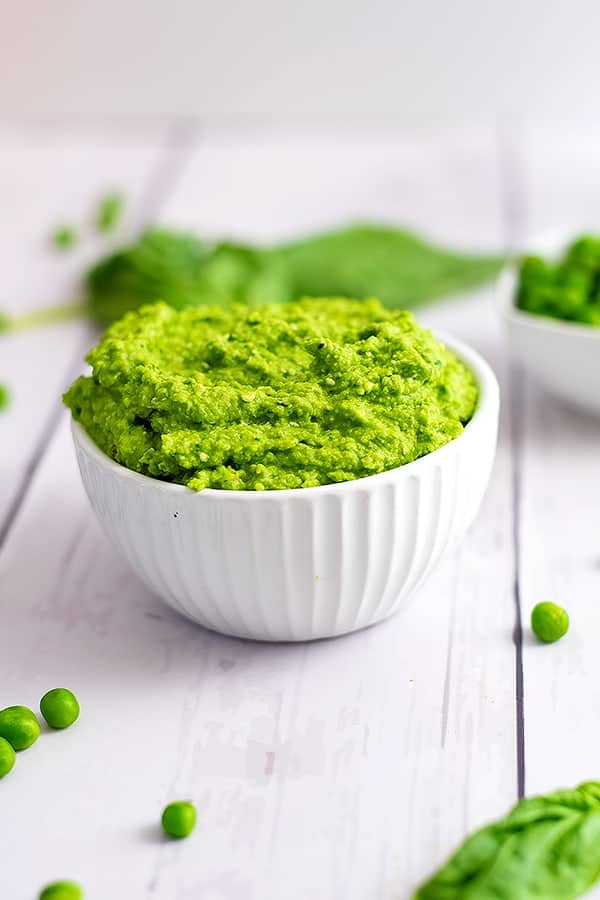 Close up shot of the bowl of pea pesto with basil in the background