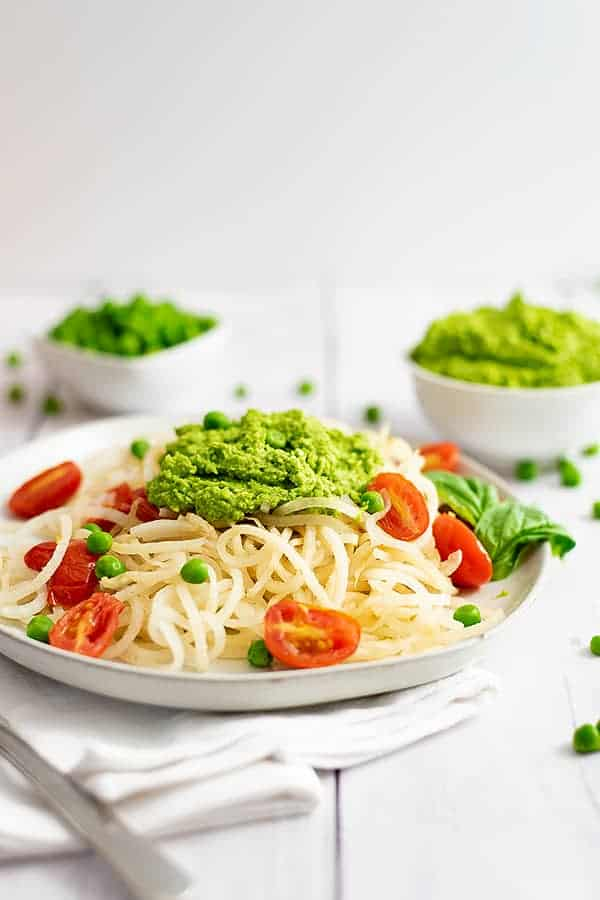 Plate filled with pasta noodles and tomatoes topped with pea pesto. Bowl of pea pesto in the background