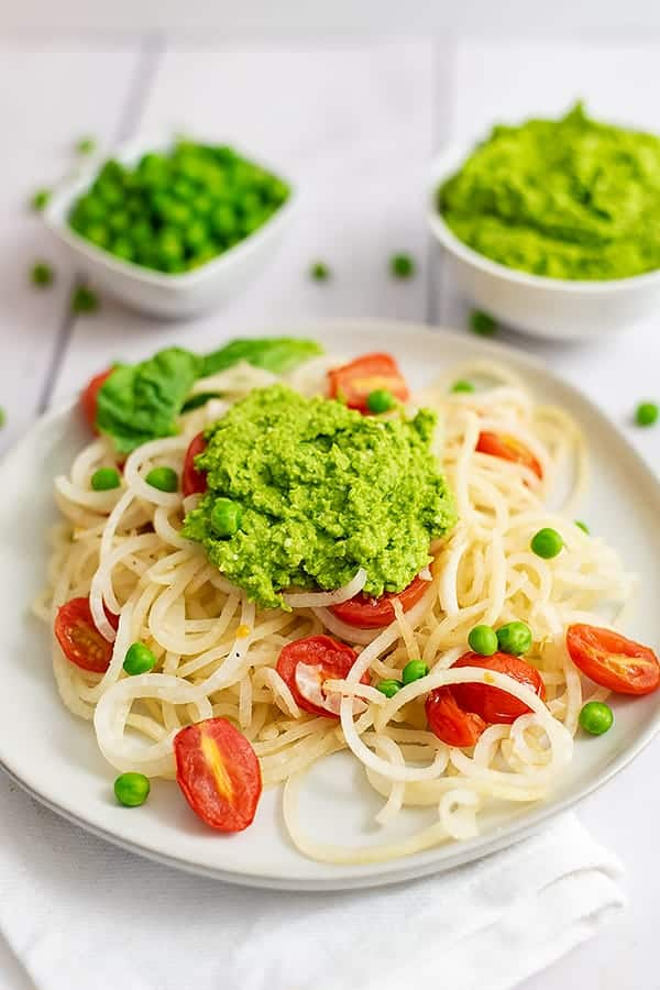 Overhead shot of a plate filled with pasta and tomatoes topped with pea pesto