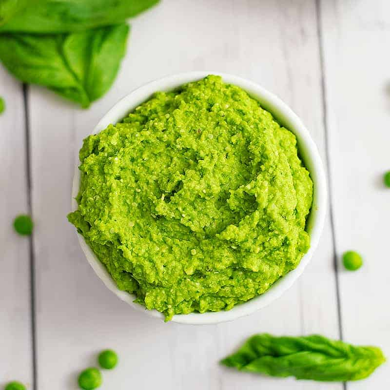 Overhead shot of a bowl filled with pea pesto with peas and basil leaves around the bowl