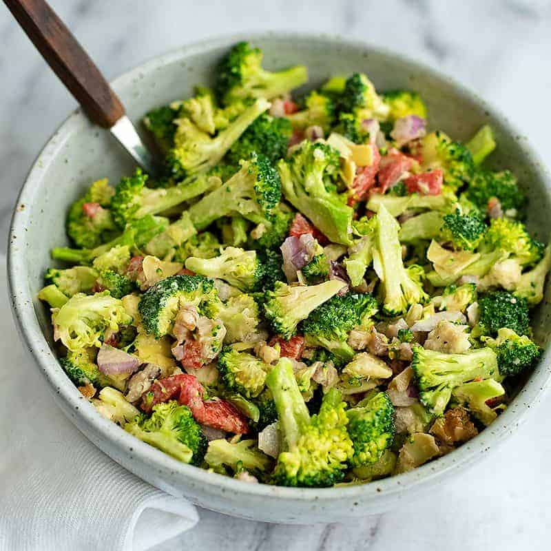Overhead shot of a bowl filled with crunchy broccoli salad with lemon tahini dressing with a wooden spoon in the bowl