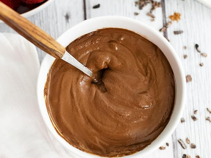 Overhead shot of a bowl of chocolate protein pudding with a wooden handled spoon in the bowl. Strawberries in the background
