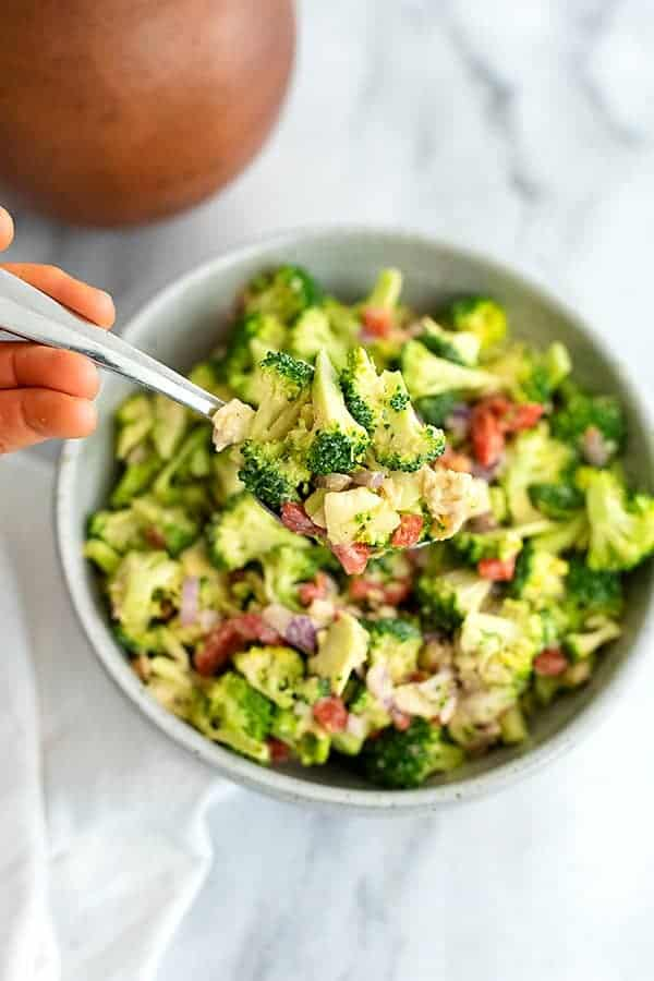 Overhead shot of a bowl filled with crunchy broccoli salad with lemon tahini dressing with a spoon being held into the salad bowl
