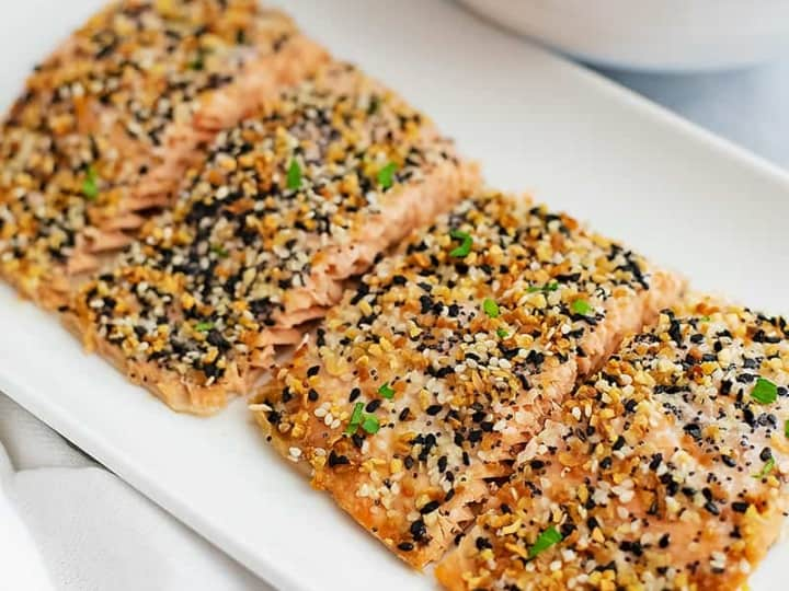 Everything bagel salmon cooked to perfection on a white square plate