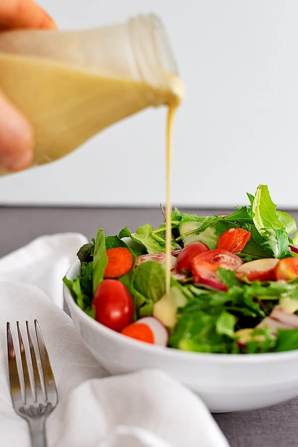 Bottle of honey mustard dressing being poured over a salad