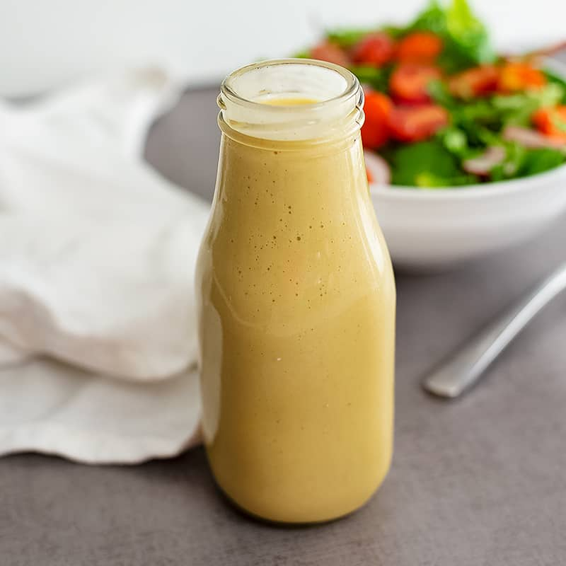 Glass bottle filled with homemade honey mustard dressing recipe with a salad in the background