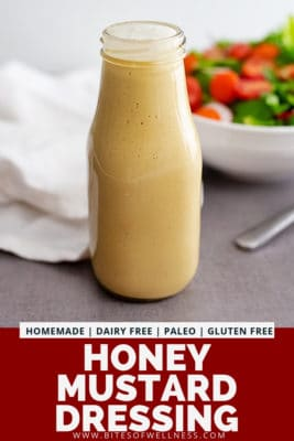 Glass bottle filled with homemade honey mustard dressing recipe with a salad in the background. Pinterest text on the bottom