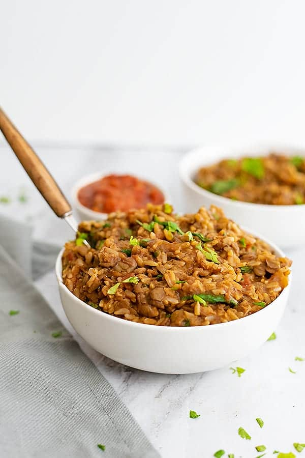 Bowl of Mexican Rice and Lentils with a wooden handled spoon