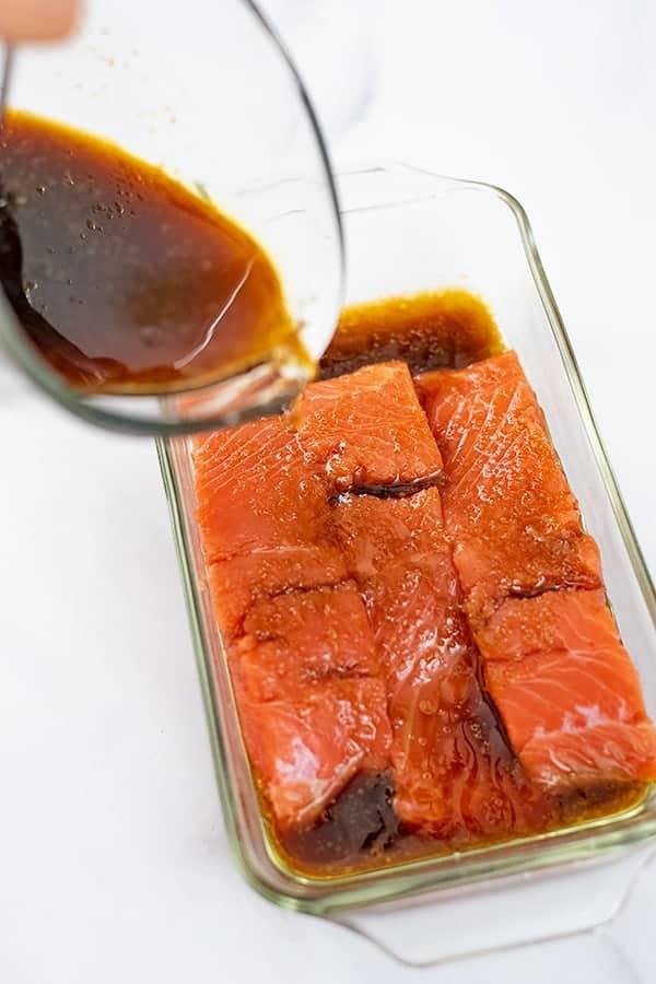 Teriyaki sauce being poured over salmon