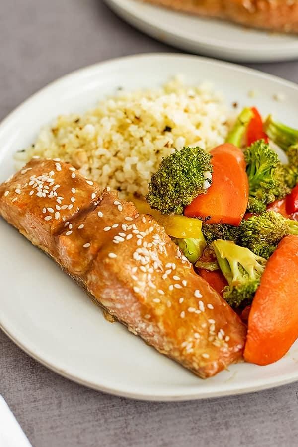 Baked teriyaki salmon, veggies and cauliflower rice on a large white plate.