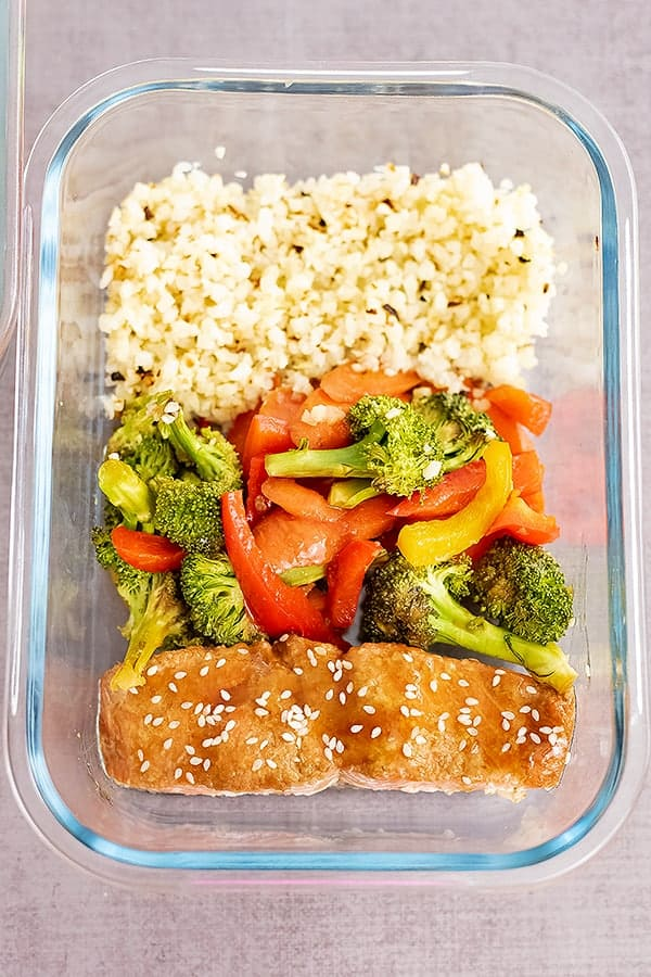 Glass storage container filled with baked teriyaki salmon, mixed veggies and cauliflower rice