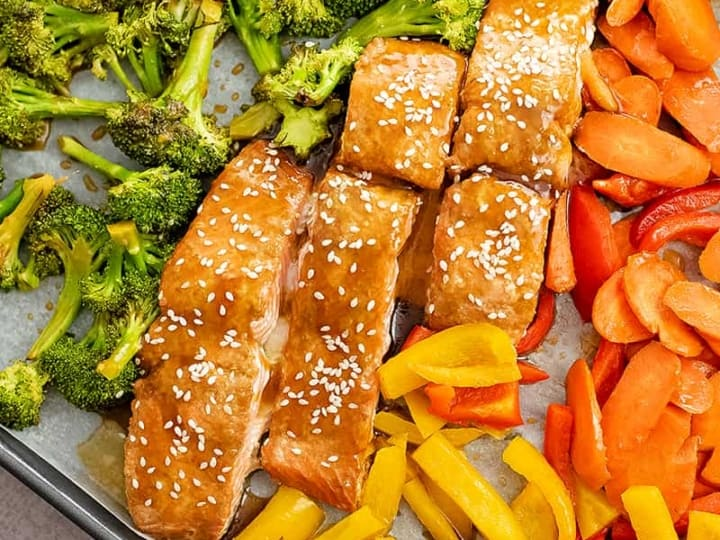 Close up of baked teriyaki salmon surrounded by chopped vegetables (broccoli, carrots, bell peppers).